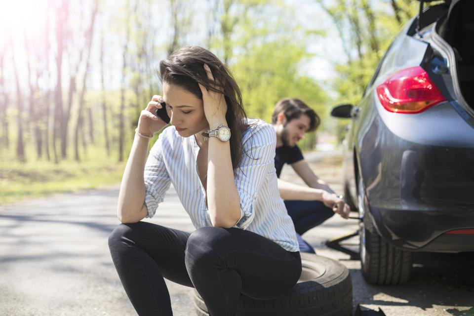 Young couple flat tire on the road