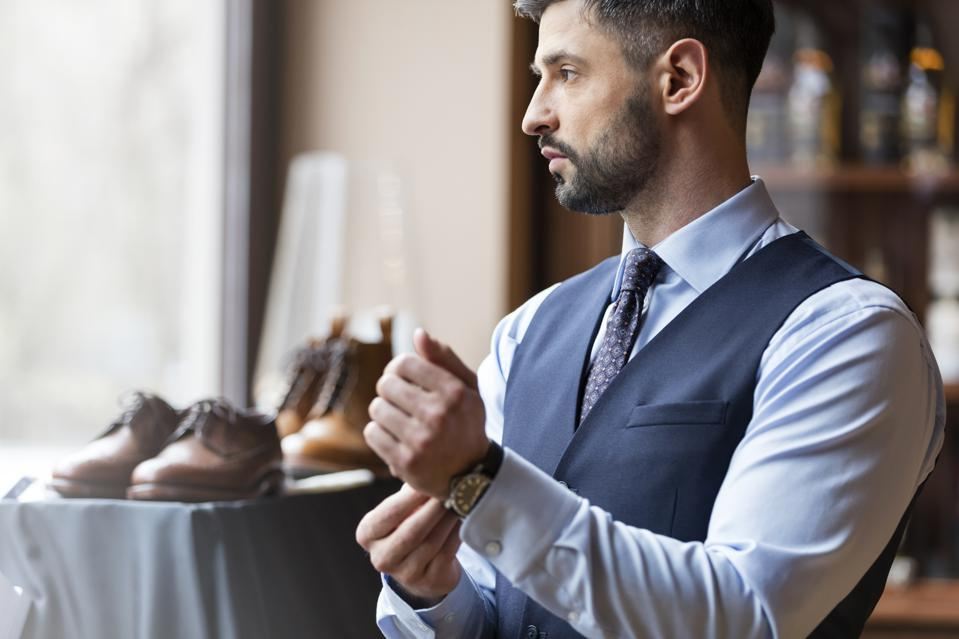 Businessman looking through window in menswear shop