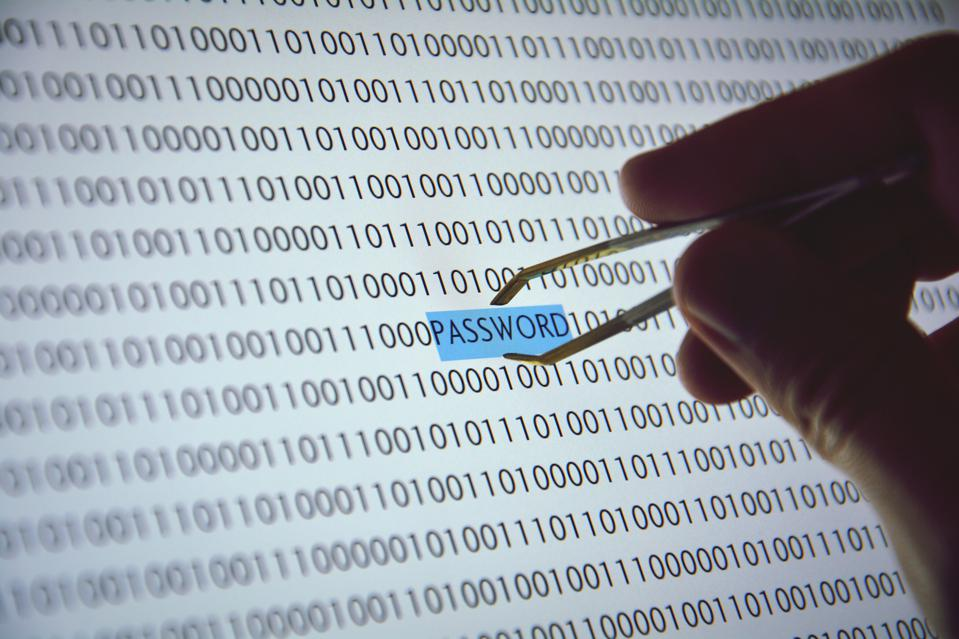 Close-Up Of Hand Holding Tweezers Over Screen With Password And Binary Code