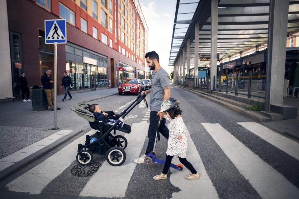Вид збоку батька, що перетинає вулицю з дочкою, тримаючи дитячу коляску в місті