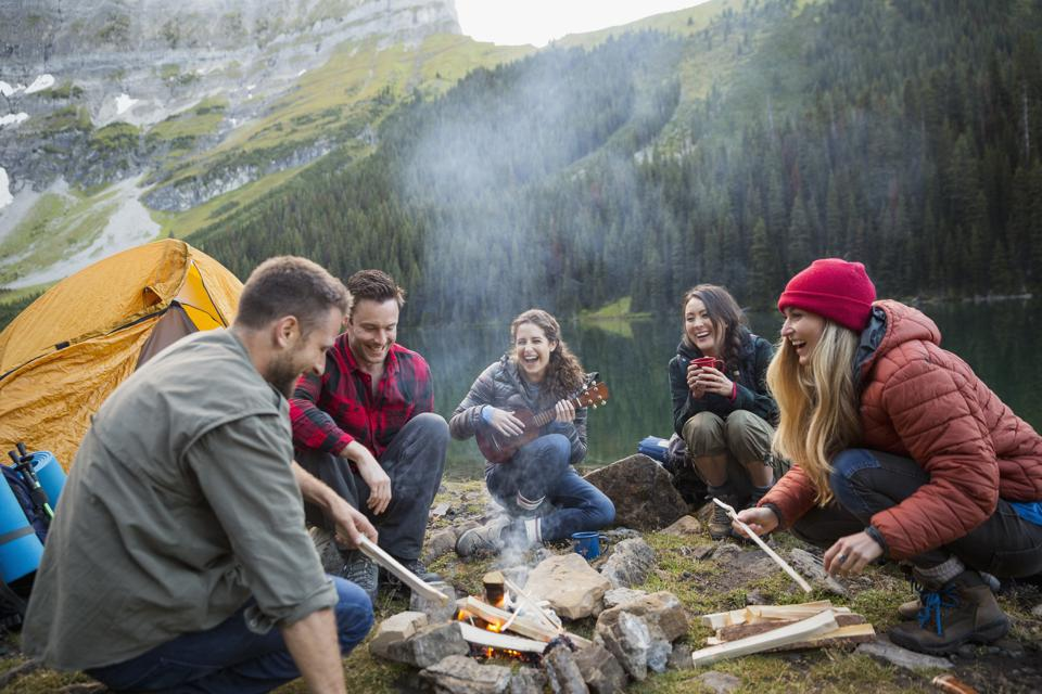 Friends laughing and hanging out around campfire at remote lakeside