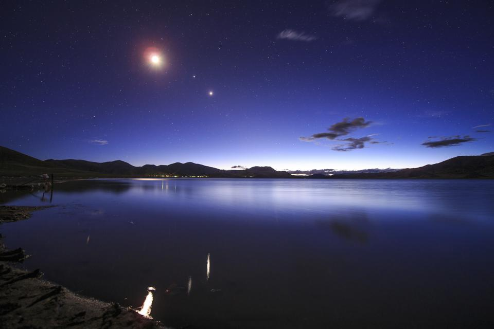 Conjunction of the moon, Jupiter and Venus above Yamdrok Lake in Tibet, China.