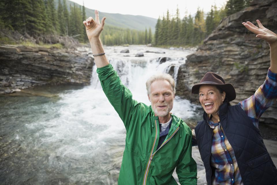 Portrait playful senior couple cheering at waterfall
