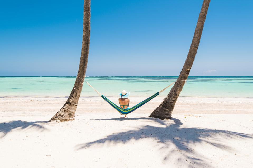 Woman relaxing on hammock on a tropical beach.