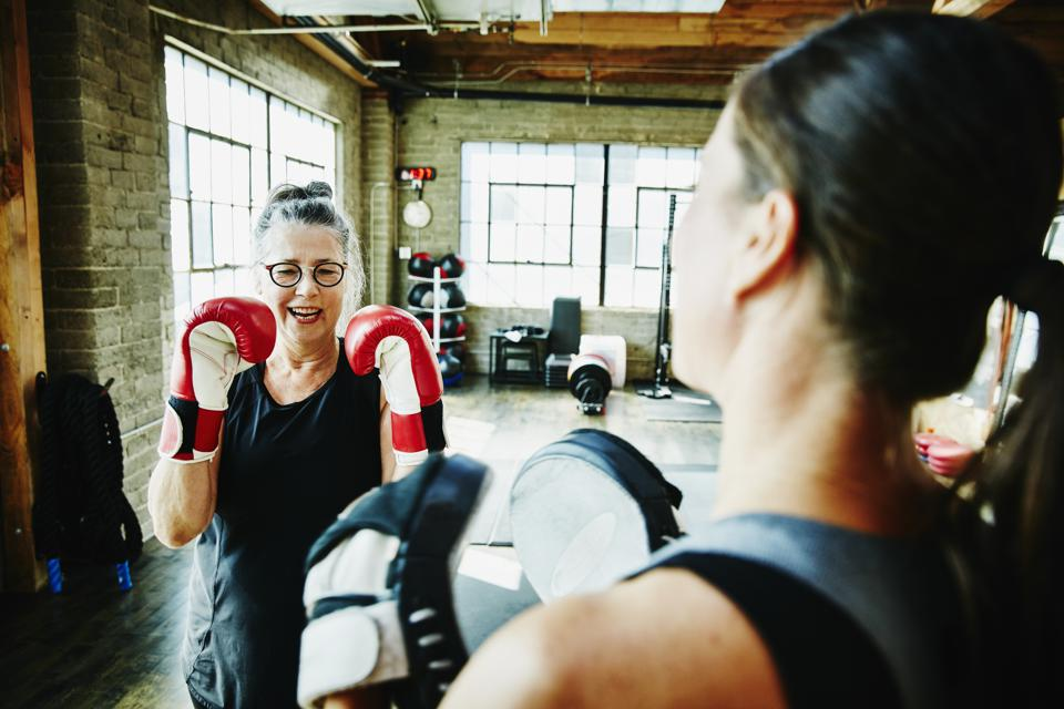 Laughing mature woman boxing with coach in gym