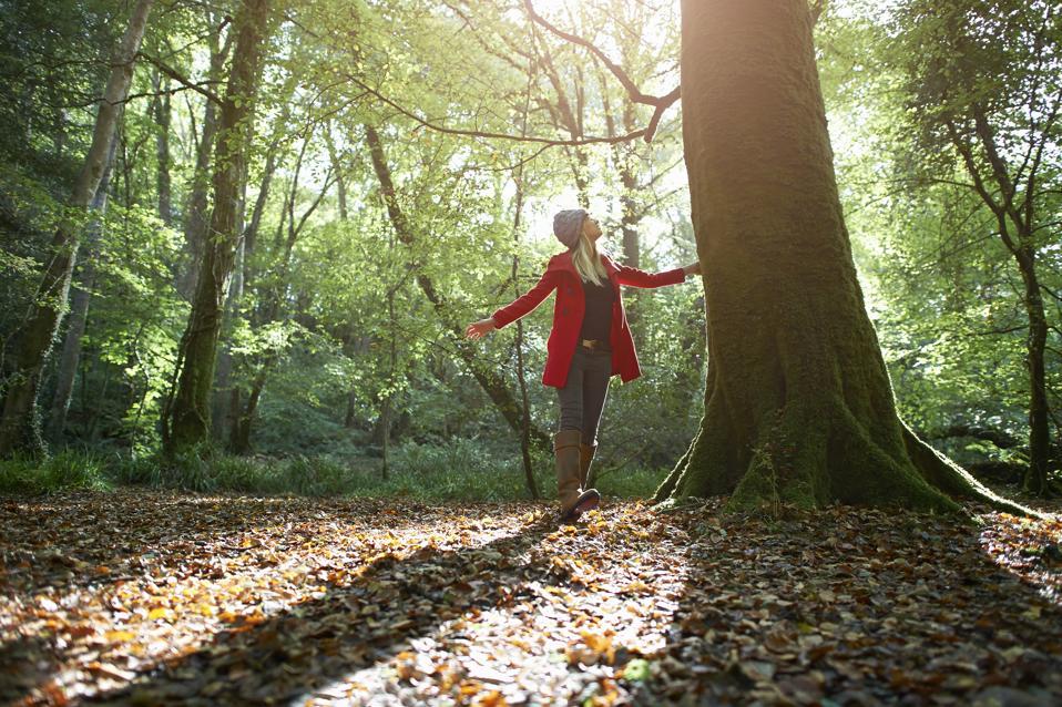 Woman walking through Autumn forest.