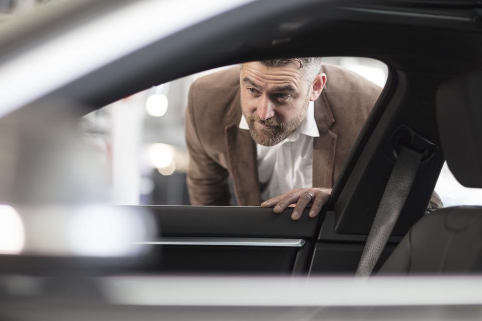 Man looking into car in car dealership