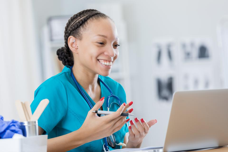 Cheerful female doctor video chats with colleague