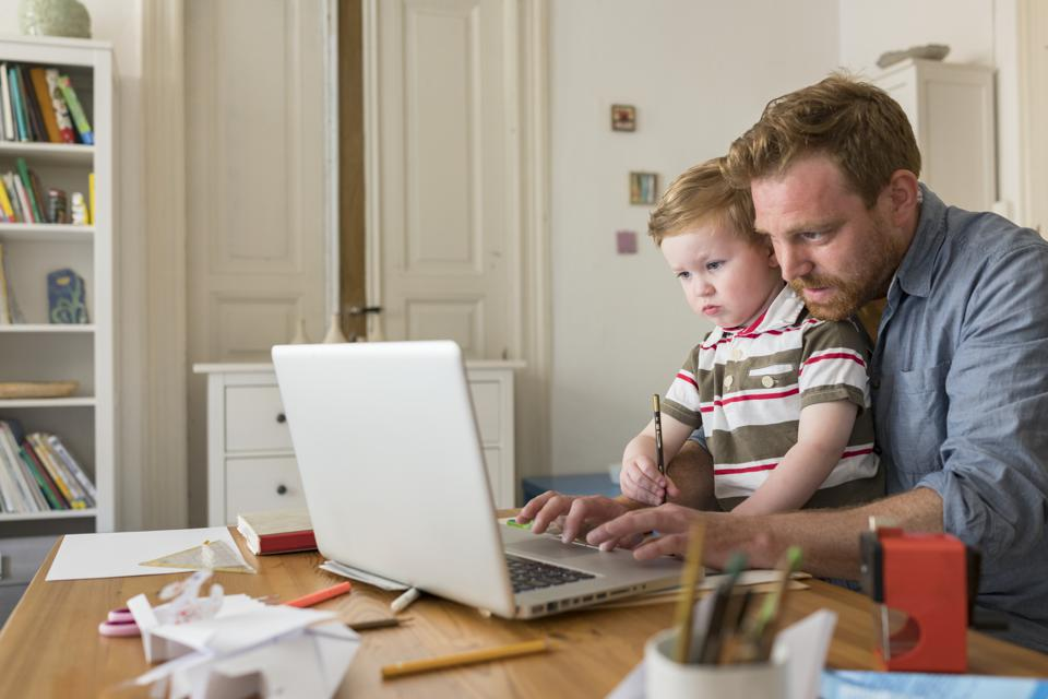 Professional with toddler son working at home