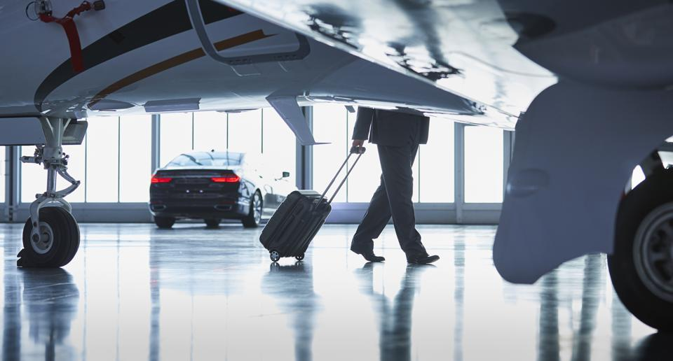 Businessman pulling suitcase outside corporate jet