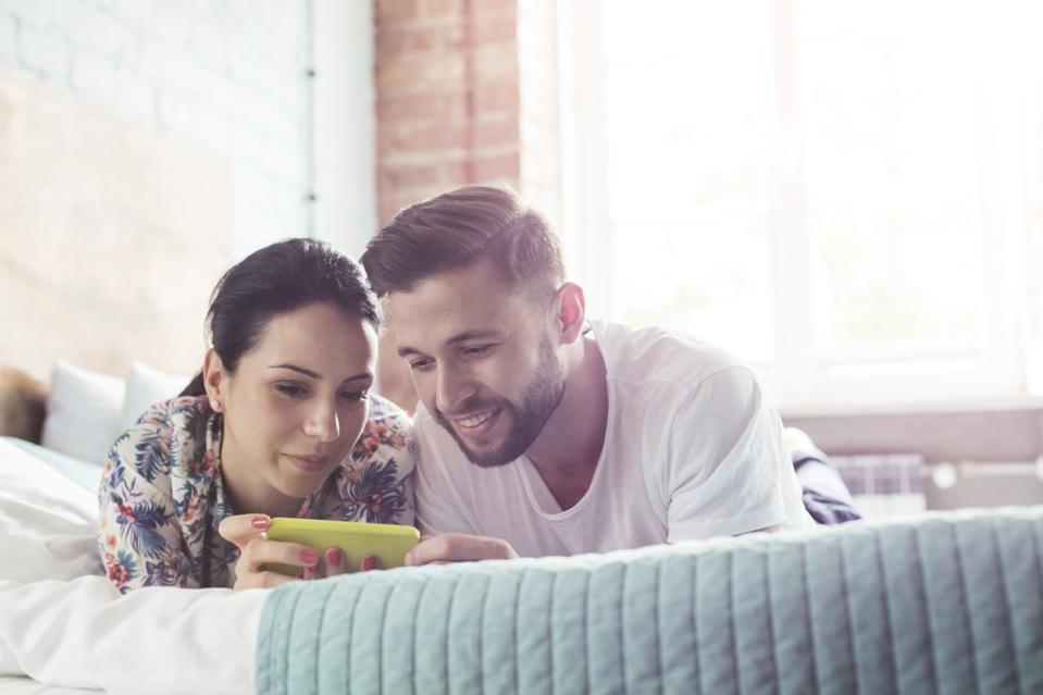 Couple using cell phone on bed