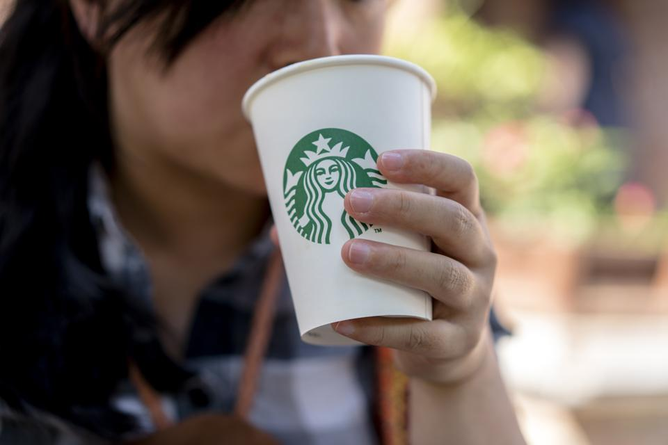 A girl holds a Starbucks coffee cup, resting at roadside...