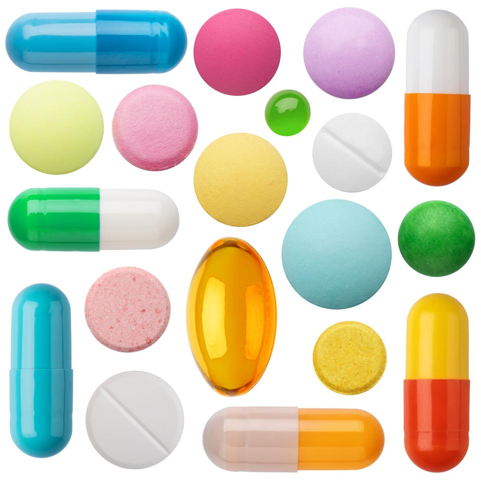 Many colorful pills and tablets isolated on white.