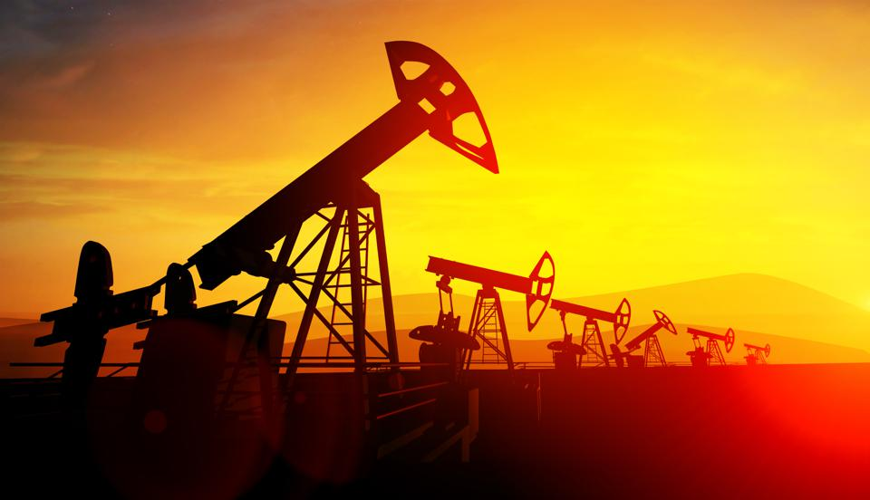 Oil pump jacks on sunset sky background. Concept of growing oil prices