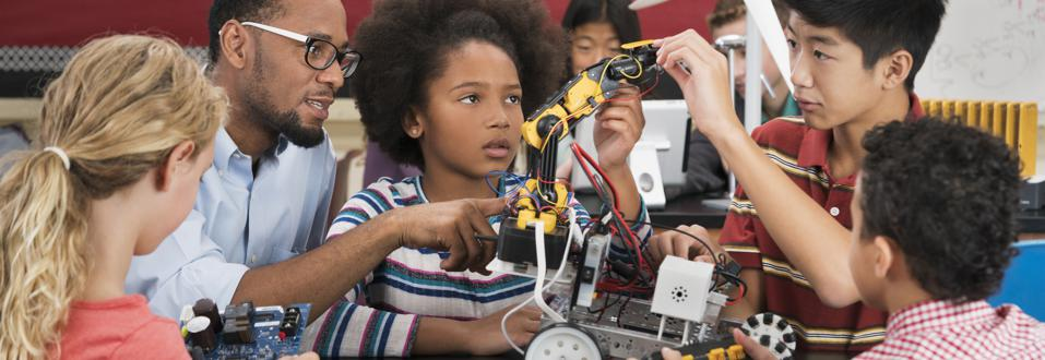 Teacher helping students with robotics in classroom