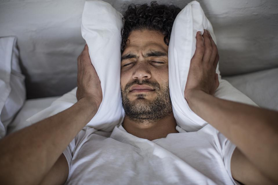 Young man covering his ears with a pillow