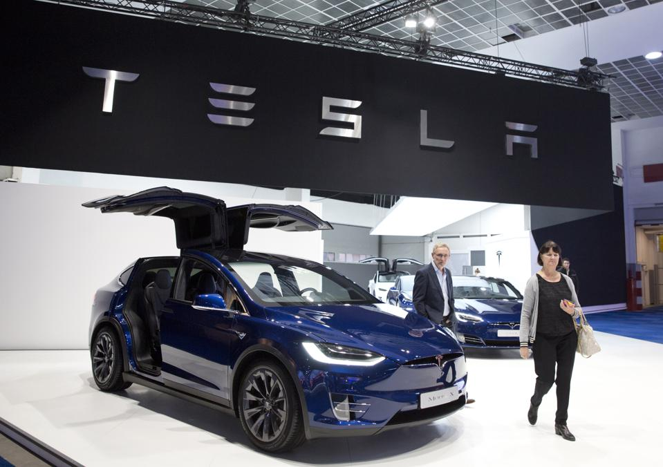 A couple walk by a Tesla Model X crossover at the Brussels Auto Show on Jan. 18, 2019, the day the company announced plans to cut its workforce by 7%.