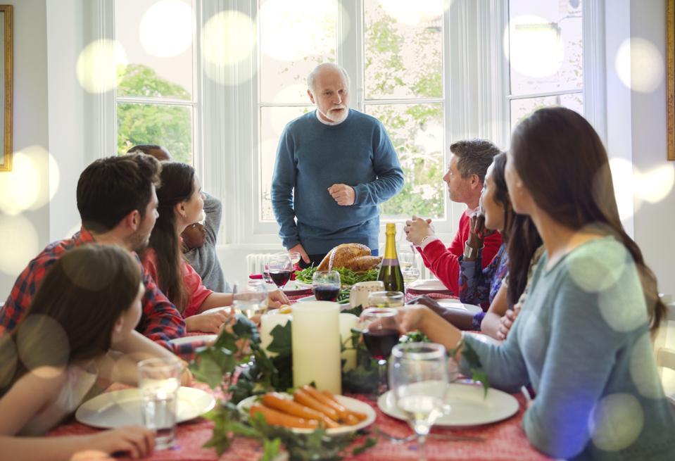 Großvater, der sich vorbereitet, Weihnachtstruthahn am Abendtische zu schnitzen