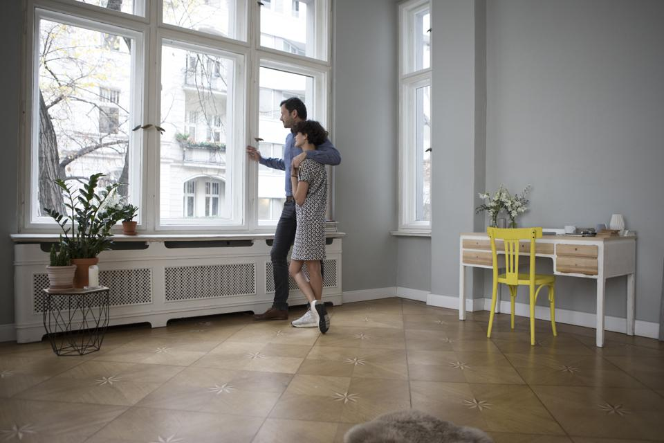 Couple looking together through window at home