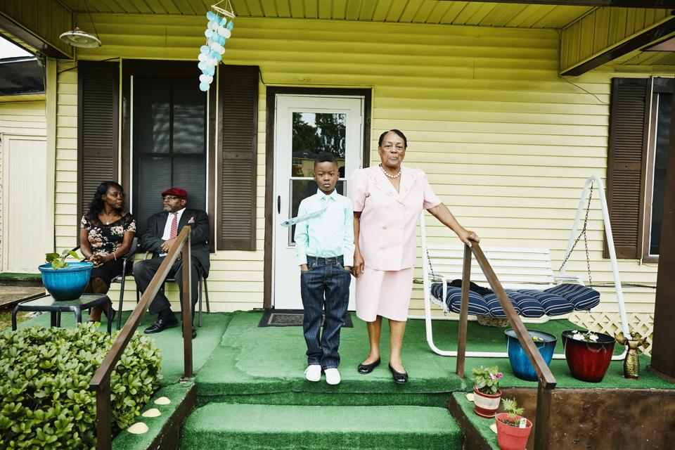 Young boy standing with grandmother on front porch of home