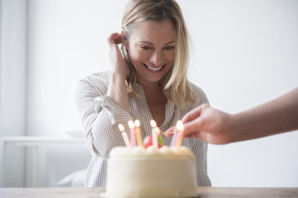 Friend lighting candles on birthday cake for Caucasian woman