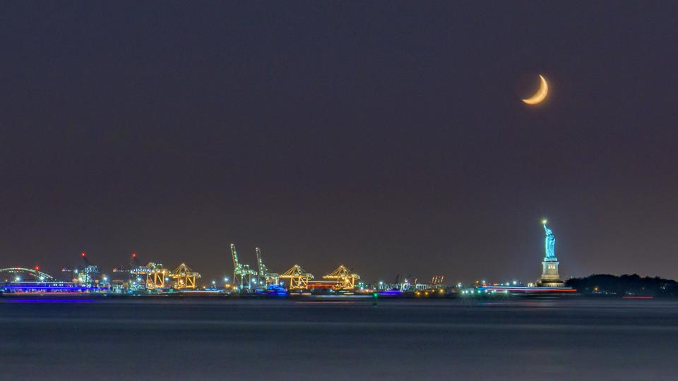 Statue Of Liberty And Illuminated Dock Against Half Moon At Night