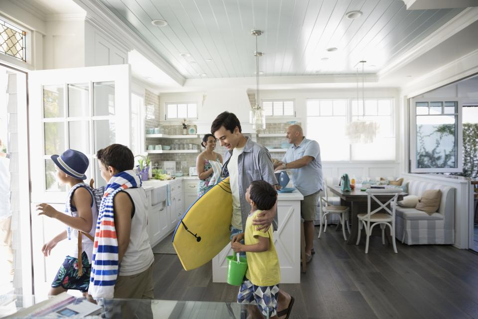 Family with body board and beach towel leaving beach house