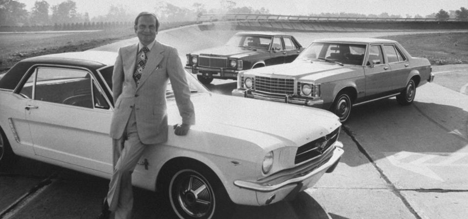 Ford Motor Co. President Lee A. Iacocca, leaning against a Ford Mustang.