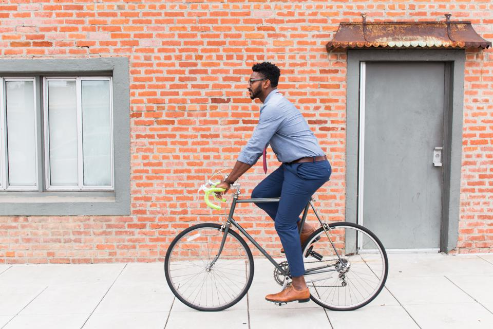 Side view of young man cycling along sidewalk