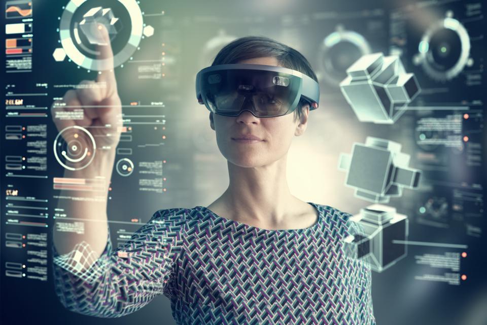 Woman wearing mixed reality smartglasses touching transparent screen