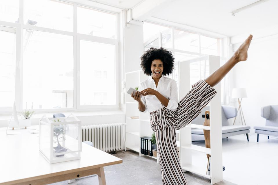 Physical exercise businesswoman dancing in office
