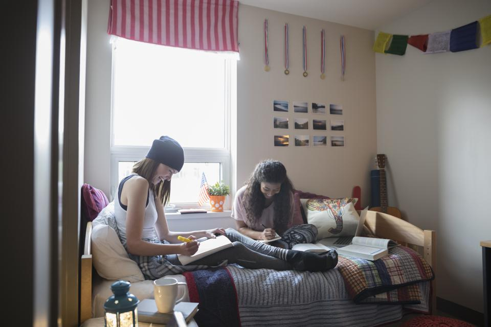 Female college students studying on bed in dorm room