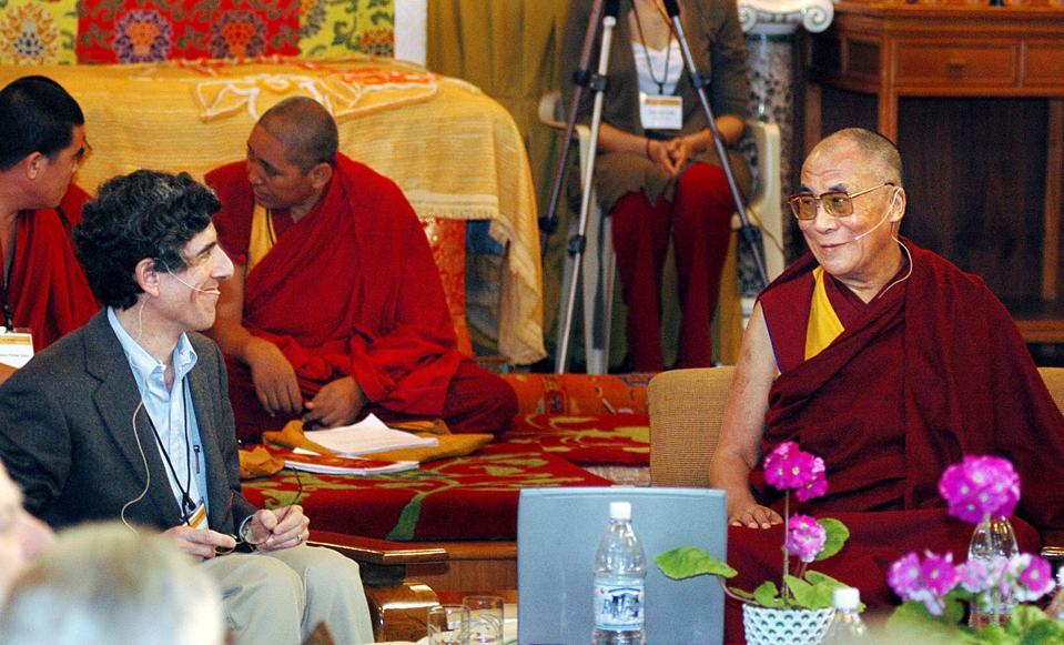 The Dalai Lama (R) smiles at Dr. Richard...