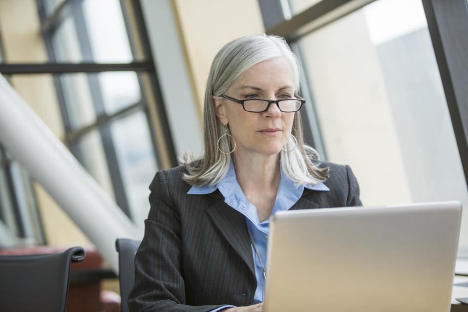 Serious Caucasian businesswoman using laptop