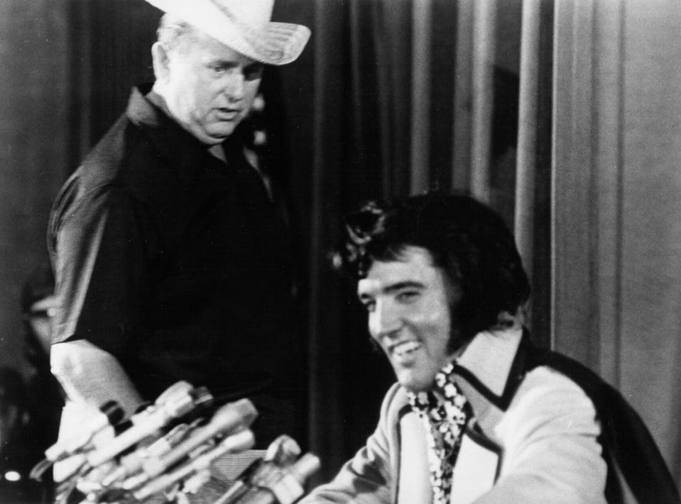Rock and roll singer Elvis Presley holds court at a press conference while Colonel Tom Parker