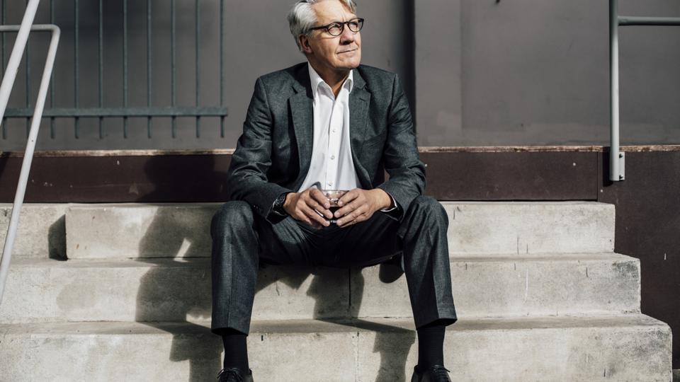 Senior businessman sitting on concrete stairs