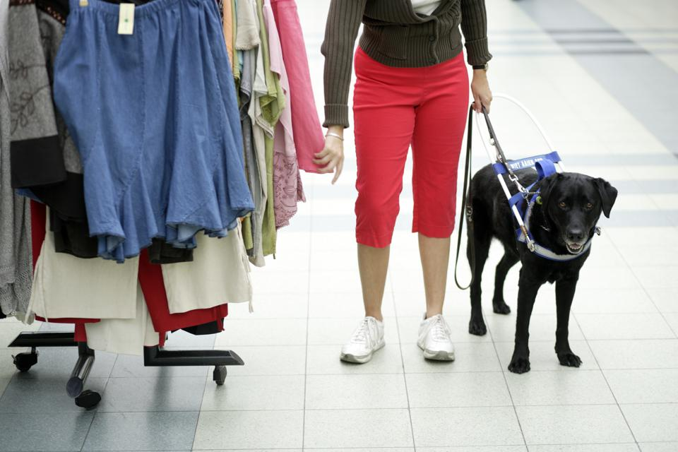 Blind woman and seeing eye dog shopping for clothing