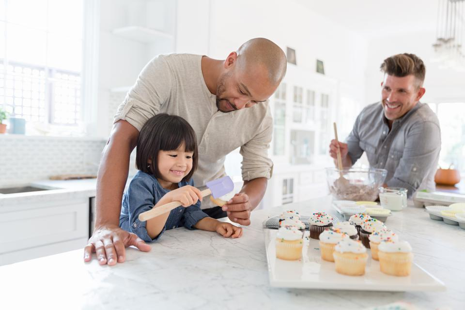 Male gay parents and adopted toddler daughter baking cupcakes in kitchen