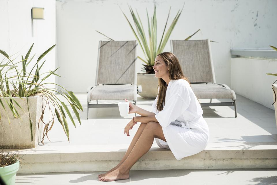 A woman wearing a bathrobe sitting on a terrace in front of loungers.