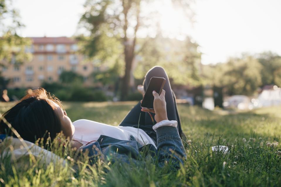 Teenage girl using smart phone while lying on grass