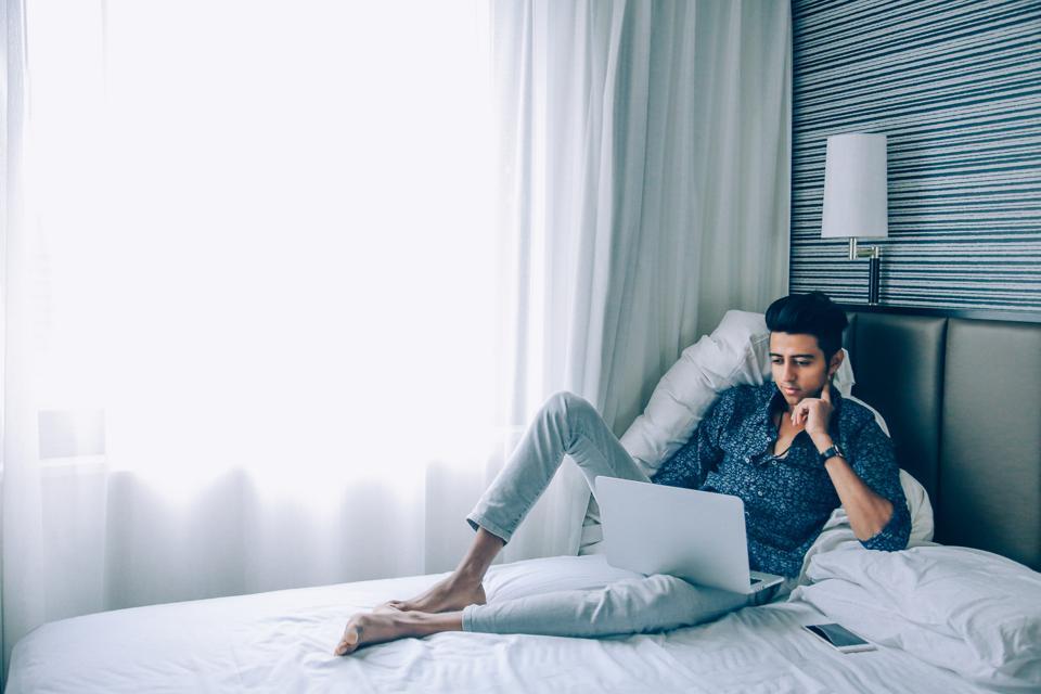 Man Using Laptop While Sitting On Bed