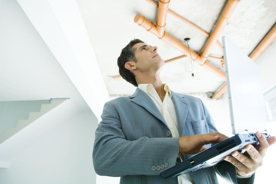 Well-dressed man using laptop, inspecting unfinished home interior