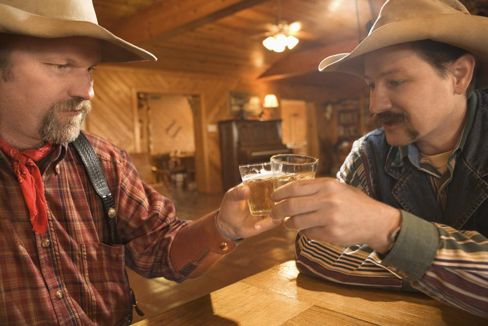 Cowboys drinking whiskey in saloon