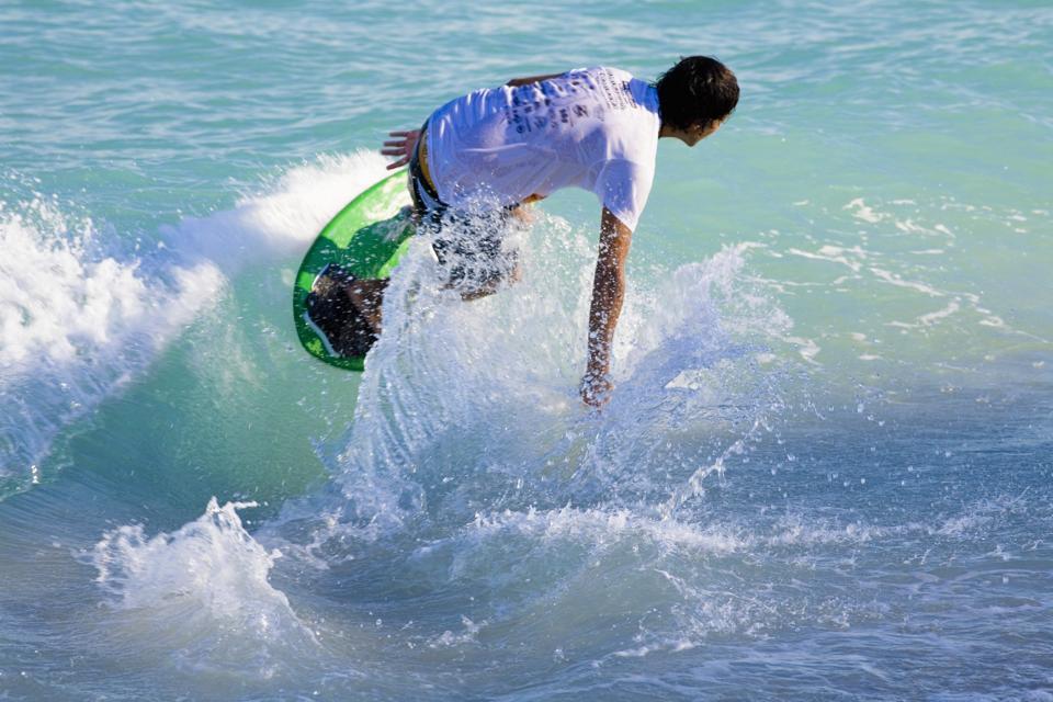 Rear view of a man on a surfboard, South Beach, Miami, Florida, USA