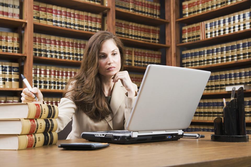 Hispanic woman looking at laptop