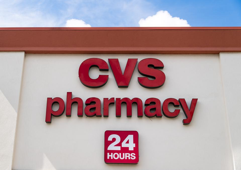 Red metal signage of CVS pharmacy, a 24 hours open medical...