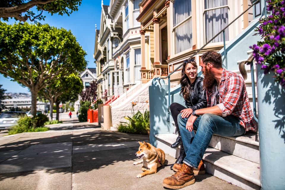 A couple with a dog on a city walk in San Francisco