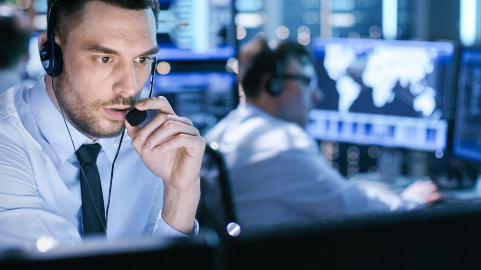 In Monitoring Room Technical Support Specialist Speaks into Headset. His Colleagues are Working in the Background.