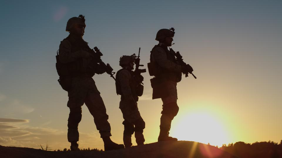 Squad of Three Fully Equipped and Armed Soldiers Standing on Hill in Desert Environment in Sunset Light.