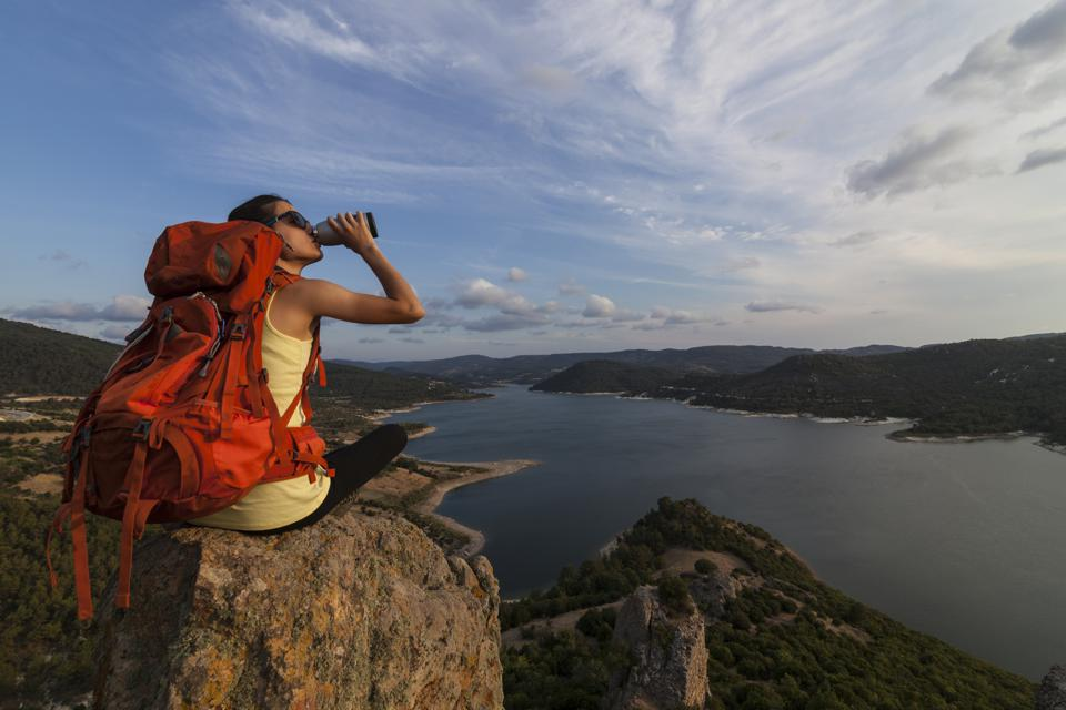 Female hiker drinking water on the top of a rock